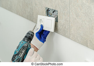 Electrician installs electrical outlet.