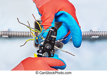 Electrician is stripps wires with stripper tool.
