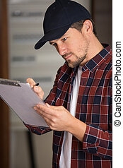 electrician looking at fuse box holding clipboard