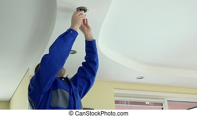 electrician professional man change LED light bulb in the ceiling in client room. 4K