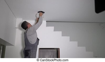 Electrician man connect wire and install led light lamp into ceiling hole