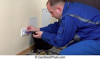 electrician man install a wall power socket