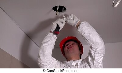 Electrician man with cutter tool removing insulation from wires in ceiling