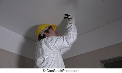 Electrician man with handsaw cutting hole in ceiling for...