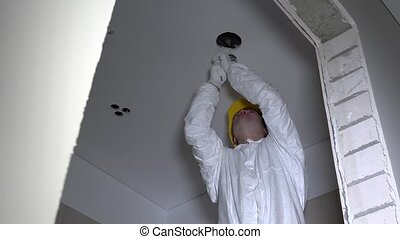 electrician man with helmet cut holes in plasterboard ceiling for lighting installation. Man with handsaw. Static shot. 4K UHD