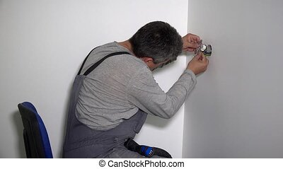 Electrician man with screwdriver connect electrical socket...