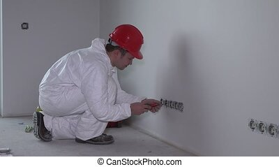 Electrician man with screwdriver repairing socket outlet wall mount in new house