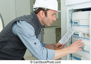 electrician reading the fuse box manual