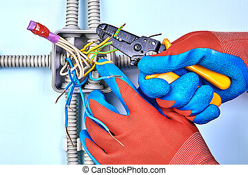 Electrician removes insulation from wires.