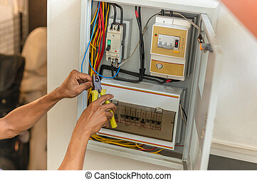 Electrician repairing electrical box with pliers at home.