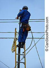 Electrician repairs lines - Electrician climbs a ladder in ...