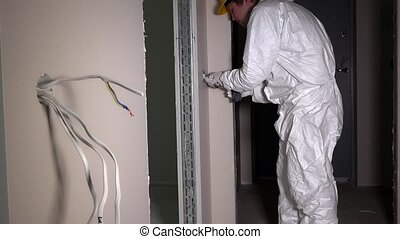 Electrician screw light switch with electrical drill. Man in...