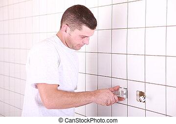 electrician screwing plug