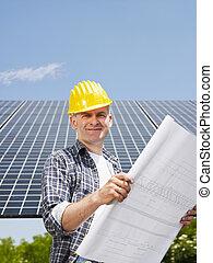 electrician standing near solar panels - Portrait of mid...