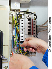 electrician - hands of an electrician measuring electrical...