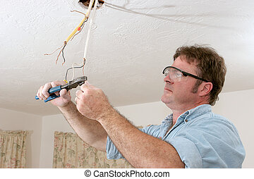 Electrician Straightents Wire - An electrician uses pliers...