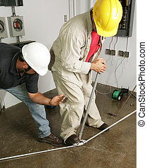Electrician & Supervisor Bend Pipe - An electrician bending...