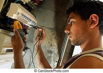 Electrician taking reading from fuse box