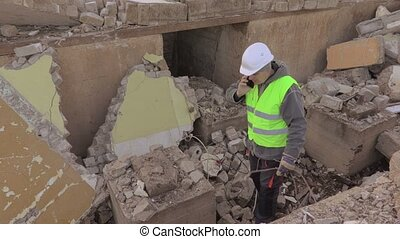 Electrician talking on smart phone at building ruins