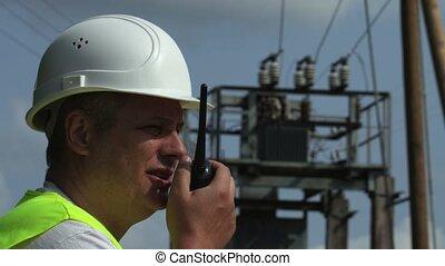 Electrician talks on walkie-talkie at high voltage transformator