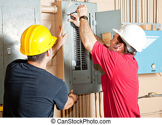 Electrician Teamwork - Electricians working together to...