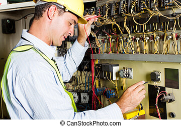 electrician testing industrial machine - male caucasian...