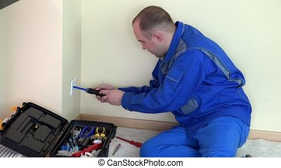 electrician unscrew outlet and test voltage with indicator in apartment