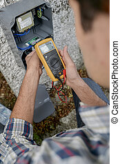Electrician using a voltmeter device
