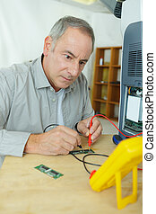 electrician using digital multimeter to check electric systems