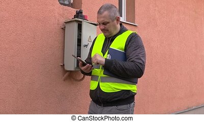 Electrician using tablet near fuse box