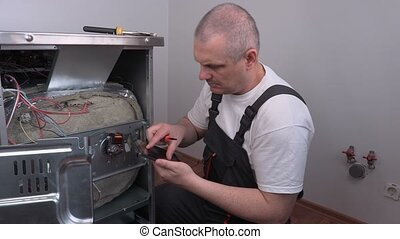 Electrician using tablet PC near electric cooker