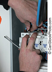 Electrician wiring a fuse box