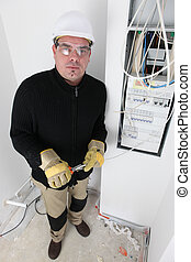 Electrician wiring a fusebox