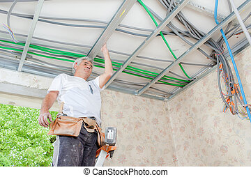 Electrician wiring a garage ceiling