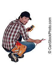 Electrician with a multimeter