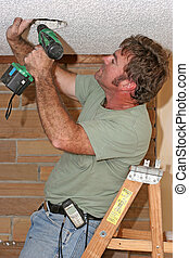Electrician With Drill - An electrician on a ladder drilling...