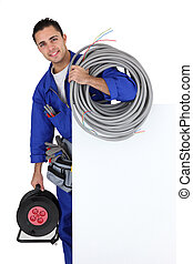 Electrician with extension cable stood by poster