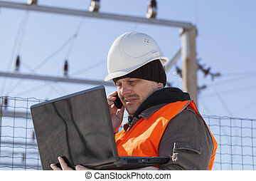 Electrician with PC and cell phone near the electricity substation