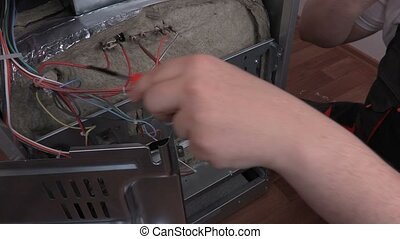 Electrician with screwdriver and smart phone near electric cooker