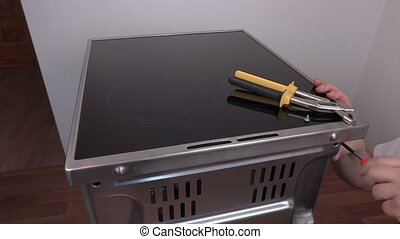 Electrician with screwdriver near electric cooker