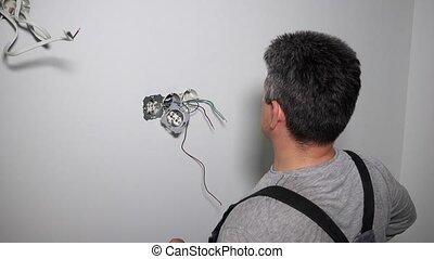 Electrician with screwdriver setting up outlet. Concept of...