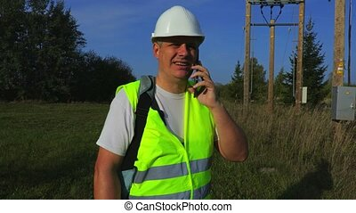 Electrician with smartphone at the transformer