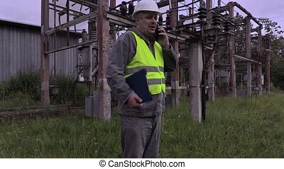 Electrician with smartphone and documentation walking in...