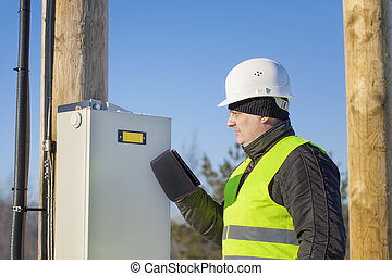 Electrician with tablet PC inspect electric lines