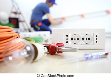 electrician work with electrical equipment in the foreground, bulb, tools and socket, electric circuits, electrical wiring