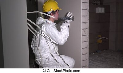 electrician worker at cable and light switch wall outlet socket installation
