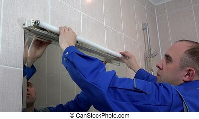Electrician worker man replace long fluorescent lamp in bathroom at client home.