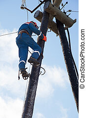 Electrician working at height against the blue sky