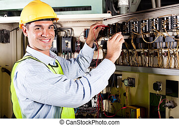 electrician working on industrial machine - happy male...