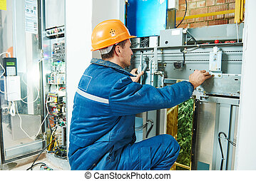 Electrician works with elevator lift equipment